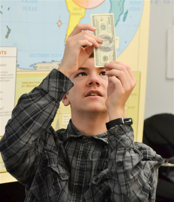student looking at counterfeit money